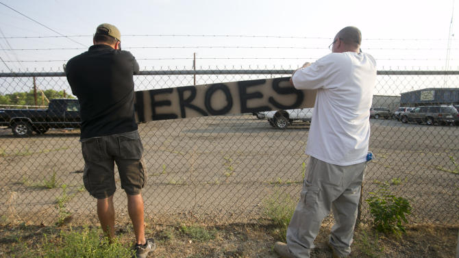Two men place a hero sign in front of Prescott Fire Station #7 on Monday, July 1, 2013, in Prescott, Ariz. Eighteen firefighters from the Prescott Fire Department's Granite Mountain Hotshots team and a 19th firefighter from another crew were killed battling the Yarnell Hill Fire on Sunday. The Granite Mountain Hotshots were based out of Prescott Fire Station #7. David Wallace/The Arizona Republic (AP Photo/The Arizona Republic, Dasvid Wallace) MARICOPA COUNTY OUT; MAGS OUT; NO SALES