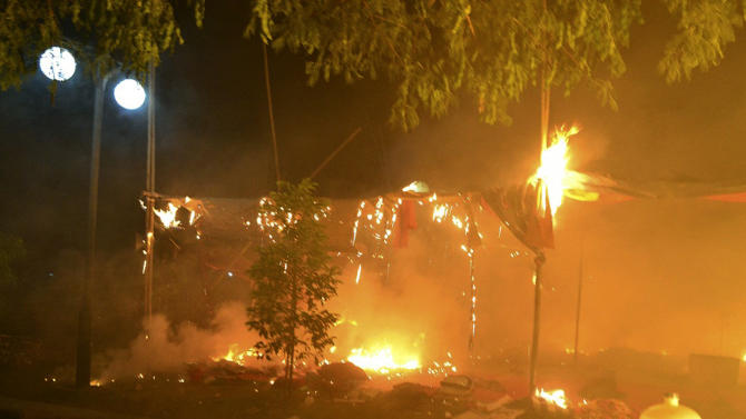 In this photo released by Eleven Media Group, flames engulf an encampment occupied by protesters at the Letpadaung mine following a crackdown by security forces near the town of Monywa, early Thursday, morning, Nov. 29, 2012. Security forces used water cannons and other riot gear Thursday to clear protesters from the copper mine in northwestern Myanmar, wounding villagers and Buddhist monks just hours before opposition leader Aung San Suu Kyi was to visit the area to hear their grievances. (AP Photo/Eleven Media Group)