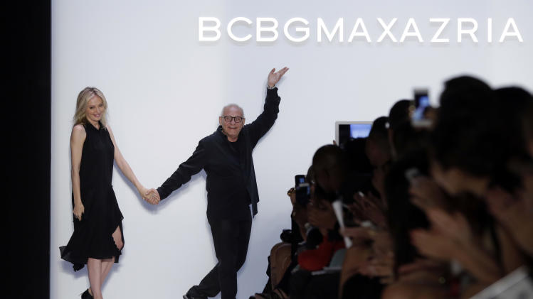 Designer Max Azria and his wife Lubov acknowledge applause after his BCBG MAX AZRIA Spring 2014 collection was modeled during Fashion Week in New York, Thursday, Sept. 5, 2013. (AP Photo/Richard Drew)