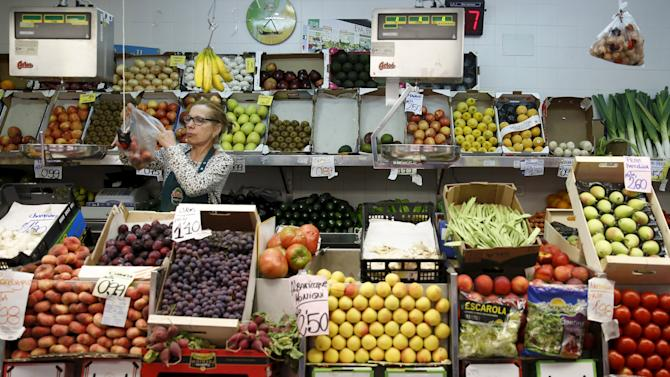 A vendor stands at a fruit and vegetable stand at the Barcelo market in Madrid, Spain