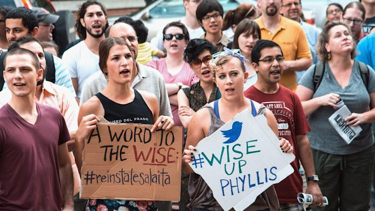 In this Aug. 26, 2014 photo, protesters at the University of Illinois in Champaign, Ill., protest against the school recently rescinding a job offer to an English professor named Steven Salaita to join the university's American Indian Studies program. Salaita had over the summer used Twitter to angrily and sometimes profanely denounce Israel during its conflict with the Palestinians. Salaita now isn't talking. But his supporters say his academic freedom was violated. (AP Photo/The News-Gazette, John Dixon) MANDATORY CREDIT