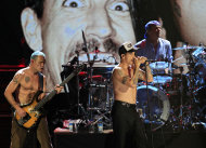 "Red Hot Chili Peppers' Mike ""Flea"" Balazary, left, singer Anthony Kiedis and drummer Chad Smith, right, perform after induction into the Rock and Roll Hall of Fame Sunday, April 15, 2012, in Cleveland. (AP Photo/Tony Dejak)"