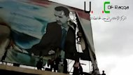 "An image from a video on YouTube shows Syrian protesters tearing a billboard of President Bashar al-Assad in Raqqa on March 4, 2013. Assad said his regime has conquered the ""conspiracy"" against it, even as rebels overran the capital of Raqa province and captured its governor in the biggest success of their revolt"