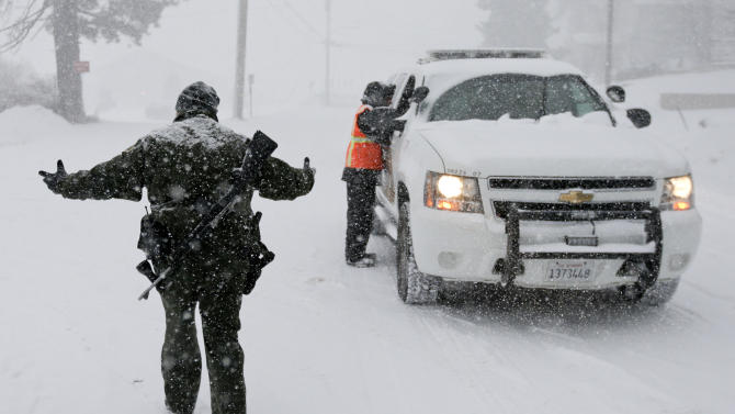 FILE - In this Feb. 8, 2013 file photo, San Bernardino Sheriff's Department offices stand guard at a checkpoint during the search for fired Los Angeles Police Department officer Christopher Dorner in Big Bear Lake, Calif. (AP Photo/Chris Carlson, File)