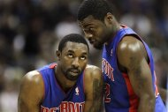 Detroit Pistons' Ben Gordon, left, and Will Bynum, right, talk while Denver Nuggets center Timofey Mozgov shoots free throws during the second quarter of an NBA basketball game on Wednesday, March 21, 2012, in Denver. (AP Photo/Barry Gutierrez)