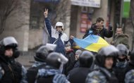 Protesters wave a Ukranian flag and gesture in front of riot police near Independence Square in Kiev November 30, 2013. REUTERS/Stoyan Nenov (UKRAINE - Tags: POLITICS CIVIL UNREST)
