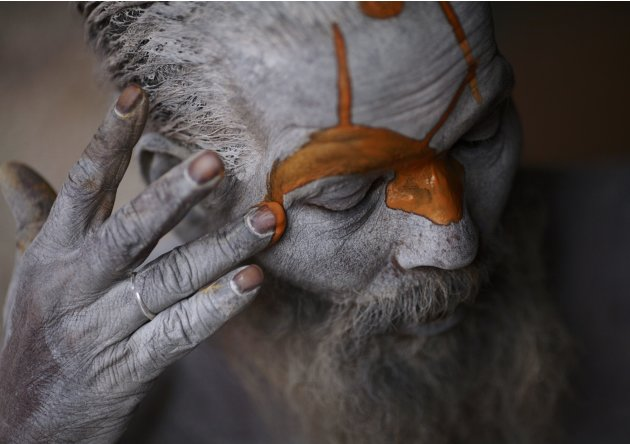 Hindu sadhu applies paint to his forehead at his ashram on the premises of Pashupatinath Temple in Kathmandu