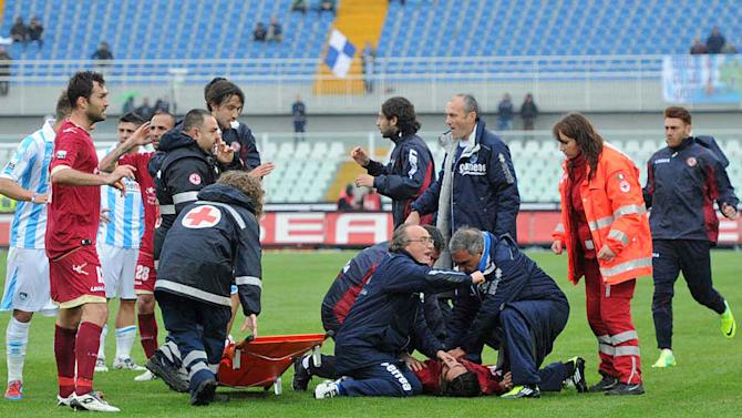Medics assists Livorno's Piermario Morosini laying on the turf of the Pescara's Adriatico stadium, central Italy, Saturday, April 14, 2012, after he collapsed during a Serie B soccer match between Pescara and Livorno. Morosini, who was on loan from Udinese, fell to the ground in the 31st minute of the match and received urgent medical attention on the pitch. A defibrillator was also used on the 25-year-old. The match was called off, with the other players leaving the field in tears. (AP Photo/Cristiano Chiodi, Lapresse)   ITALY OUT