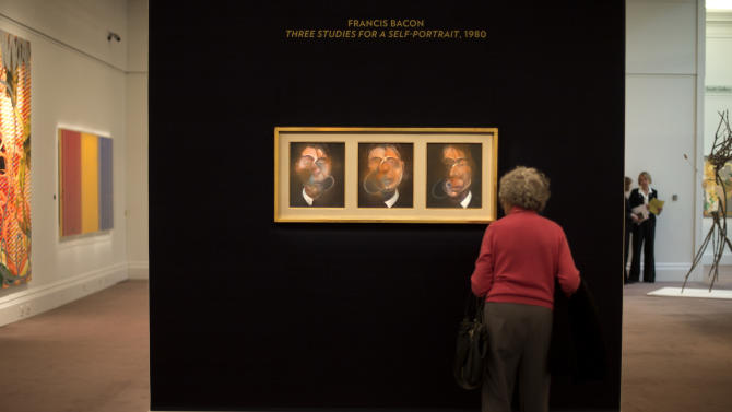 "A woman looks at a triptych by artist Francis Bacon entitled ""Three studies for a Self Portrait"" at Sotheby's auction house during a press preview in London, Thursday, Jan. 31, 2013. The work is estimated to sell for some 10 to 15 million pounds (US$ 15.8-23.7 million, euro 11.6-17.5 million )at auction on Feb. 12, in London. (AP Photo/Alastair Grant)"