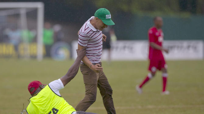 A security guard slips while trying to catch a fan who walked into the field during friendly soccer match between the New York Cosmos and Cuba at the Pedro Marrero Stadium in Havana, Cuba, Tuesday, June 2, 2015. New York Cosmos won the game 4-1. (AP Photo/Ramon Espinosa)