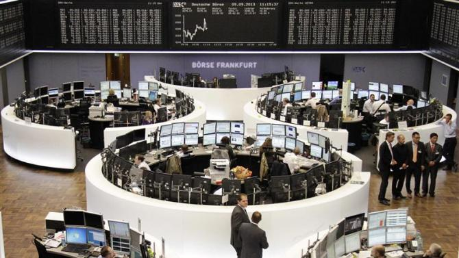 Traders are pictured at their desks in front of the DAX board at the Frankfurt stock exchange