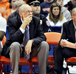 Syracuse head coach Jim Boeheim watches the game beside the empty chair of associate head coach Bernie Fine during the first half of an NCAA college basketball game against Colgate in Syracuse, N.Y., Saturday, Nov. 19, 2011. Fine was placed on administrative leave after child molestation accusations surfaced. (AP Photo/Kevin Rivoli)