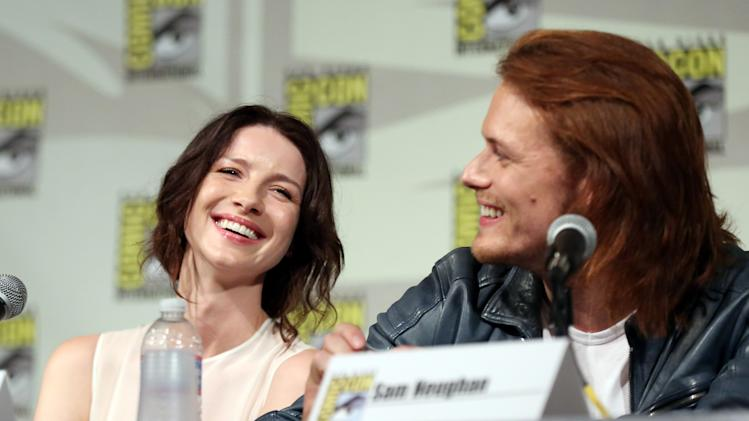 "IMAGE DISTRIBUTED FOR STARZ - Caitriona Balfe, left, and Sam Heughan are seen onstage at the STARZ ""Outlander"" panel during San Diego Comic-Con on Friday, July 25, 2014 in San Diego. ""Outlander"" premieres on STARZ August 9, 2014. (Photo by Matt Sayles/Invision for STARZ/AP Images)"