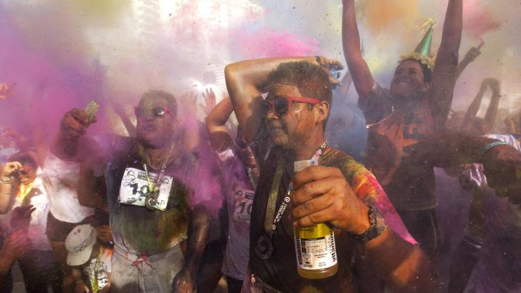 "Runners jump and throw colored powder into the air after the ""Cancun at Color"" race in the tourist destination of Cancun"
