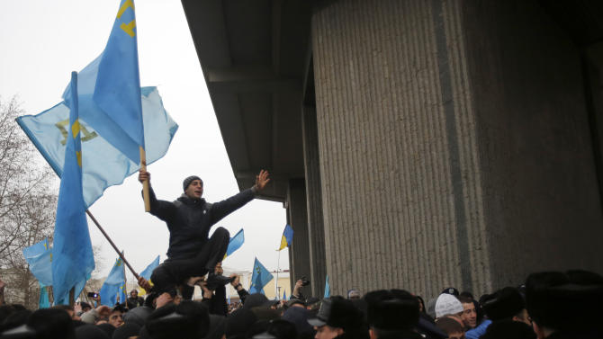 A Crimean Tatar shouts slogans and waves the ethnic flag of the Crimean Tatars during a protest in front of a local government building in Simferopol, Crimea, Ukraine, Wednesday, Feb. 26, 2014. More than 10,000 Muslim Tatars rallied in support of the interim government. That group clashed with a smaller pro-Russian rally nearby. Fistfights broke out between pro- and anti-Russian demonstrators in Ukraine's strategic Crimea region on Wednesday as Russian President Vladimir Putin ordered massive military exercises just across the border. (AP Photo/Darko Vojinovic)