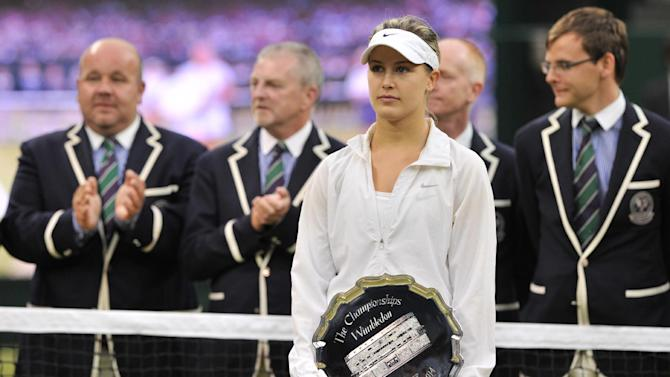 Runner up Canada's Eugenie Bouchard holds her trophy after losing to Czech Republic's Petra Kvitova in the women's singles final match on day 12 of the 2014 Wimbledon Championships in Wimbledon on July 5, 2014
