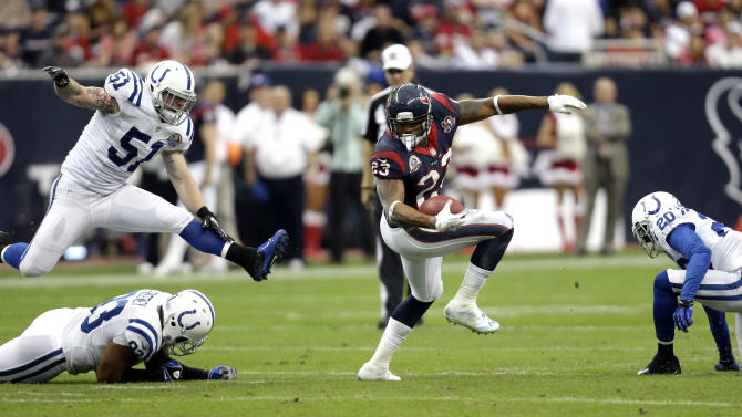Houston Texans running back Arian Foster (23) turns up field as Indianapolis Colts' Pat Angerer (51) leaps over Dwight Freeney (93) in the first quarter of an NFL football game on Sunday, Dec. 16, 2012, in Houston. Indianapolis Colts' Darius Butler (20) looks on. (AP Photo/Eric Gay)