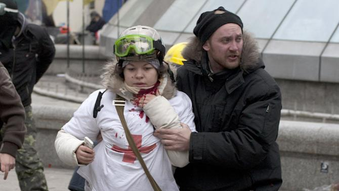 """In this Thursday, Feb. 20, 2014 photo, Olesya Zhukovska, left, is helped after being shot in her neck by a sniper bullet, in Independence Square, the epicenter of the country's current unrest, Kiev, Ukraine. """"I am dying,"""" Olesya Zhukovska, a 21-year-old volunteer medic, wrote on Twitter, minutes after she got shot in the neck by a sniper's bullet as deadly clashes broke out in the center of the Ukrainian capital between protesters and police. The tweet, accompanied by a photo of her clutching her bleeding neck and being led away under fire, went viral, as social media users around the world presumed she had died and shared their grief and anger. But Zhukovska survived. She has become a symbol of the three-month protest of President Viktor Yanukovych's government and a movement for closer ties with the West and human rights. (AP Photo/Alexander Sherbakov)"""