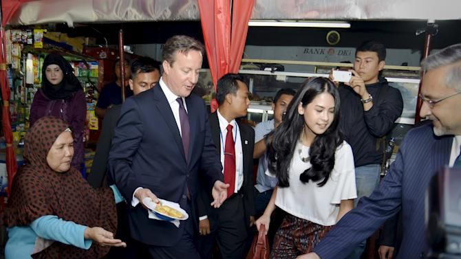 British Prime Minister David Cameron is accompanied by Indonesian entertainer Maudy Ayunda after ordering fried bananas at a street food stall after his visit to Sunda Kelapa Mosque in Jakarta