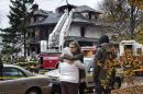 FILE - In this Nov. 1, 2014 file photo, friends of a victim of a fatal apartment building fire console one another other in Portland, Maine. Six died in the fire the morning after a Halloween party there the previous night. Documents released Friday, Nov. 7, 2014, following a Freedom of Access request by The Associated Press showed 16 complaints about the building going back about 11 years. A 2012 complaint said the owner had added a new dwelling unit on the third floor, where three bodies were found in a bedroom. The building was permitted for two units. (AP Photo/Robert F. Bukaty, File)