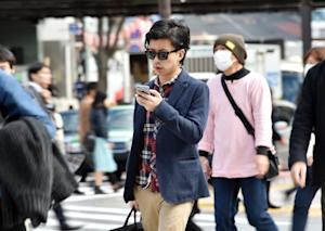 A pedestrian using his smartphone on a street in Tokyo, …