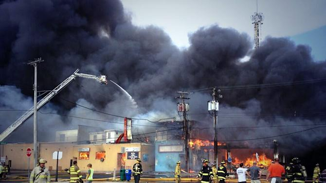 Firefighters battle a raging fire on the boardwalk in Seaside Heights, N.J. that apparently started in an ice cream shop and has spread several blocks to neighboring Seaside Heights, Thursday, Sept. 12, 2013. The boardwalk was damaged in Superstorm Sandy and was being repaired. (AP Photo/The Asbury Park Press, Kristi Funderburk) MANDATORY CREDIT: PAPER AND PHOTOGRAPHER; NO SALES