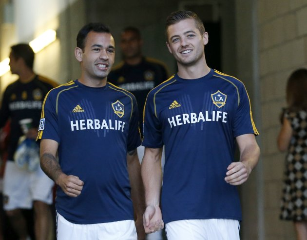Los Angeles Galaxy midfielder Robbie Rogers walks out to the pitch with teammate Juninho before their MLS soccer game