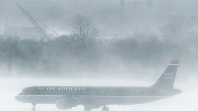 A U.S. Airways jet is seen amidst snow blown by gust of wind at the Philadelphia International Airport  in Philadelphia, Monday, Dec. 27, 2010. A powerful East Coast blizzard menaced would-be travelers by air, rail and highway Monday, leaving thousands without a way to get home after the holidays and shutting down major airports and rail lines for a second day. (AP Photo/Matt Rourke)