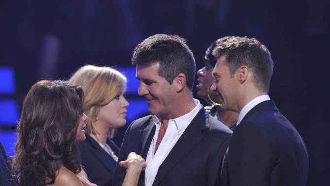"""In this May 26, 2010 photo released by Fox, """"American Idol"""" judge and producer Simon Cowell, center, is congratulated by former judge Paula Abdul, left, and host Ryan Seacrest during the singing competition finale on May 26, 2010, in Los Angeles. Musician Steven Tyler will replace Cowell as a judge next season. (AP Photo/Fox, Vince Bucci)"""