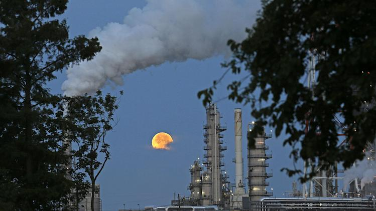 "The larger-than-normal full moon referred to as Supermoon is seen setting beyond a refinery in Norco, La., Sunday, June 23, 2013. The larger than normal moon called the ""Supermoon"" happens only once this year as the moon on its elliptical orbit is at its closest point to earth and is 13.5 percent larger than usual. (AP Photo/Gerald Herbert)"