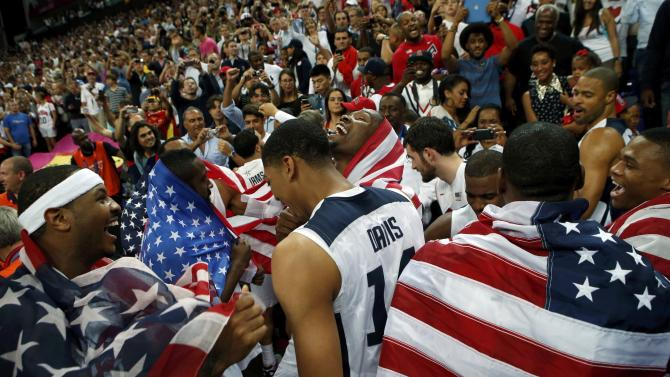 Players of the U.S. celebrates with national flags victory against Spain after their men's gold medal  basketball match at the North Greenwich Arena in London during the London 2012 Olympic Games