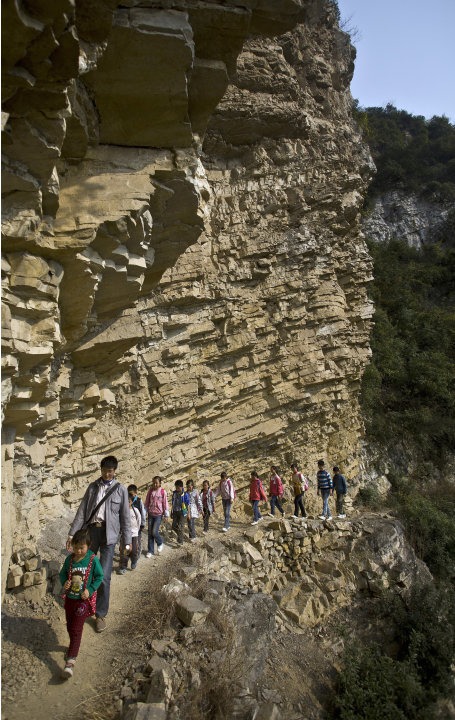 Xu Liangfan, 37, escorts students on a cliff path as they make their way to Banpo Primary School in Shengji county