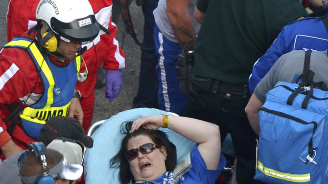A spectator, center, is transported from the grandstands by emergency personnel after Kyle Larson's car hit the safety wall and fence along the front stretch on the final lap of the NASCAR Nationwide Series auto race at Daytona International Speedway in Daytona Beach, Fla., Saturday, Feb. 23, 2013. Several fans were injured when large chunks of debris flew into the grandstands. (AP Photo/Phelan M. Ebenhack)