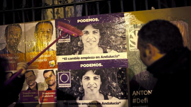 A member of Podemos puts up election posters of Podemos candidate for the region's elections Rodriguez at the start of her electoral campaign in Ronda