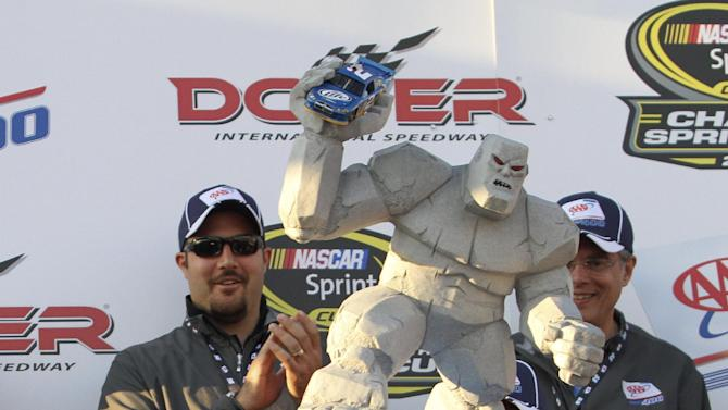 Brad Keselowski hoists the trophy as he celebrates his win in victory lane at the NASCAR Sprint Cup Series auto race at Dover International Speedway, Sunday, Sept. 30, 2012, in Dover, Del. (AP Photo/The Wilmington News-Journal, Daniel Sato)  NO SALES