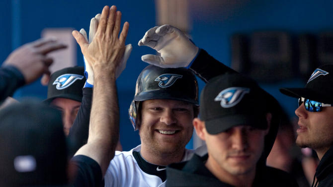 Toronto Blue Jays' Adam Lind, center, celebrates his solo home run in the second inning of MLB baseball game action against the New York Yankees in Toronto, Sunday, Sept. 18, 2011. (AP Photo/The Canadian Press, Darren Calabrese)