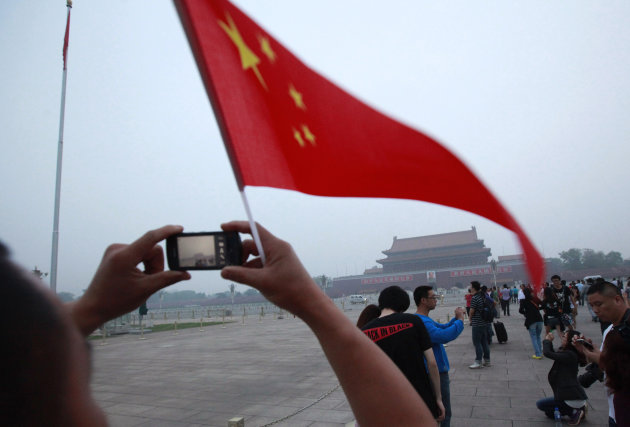 Visitors take photos near a Chinese national flag with Tiananmen Gate in the background as many gathered to mark the anniversary of the deadly 1989 crackdown on pro-democracy protestors which centered on Tiananmen Square, in Beijing, China, Monday, June 4, 2012. (AP Photo/Ng Han Guan)