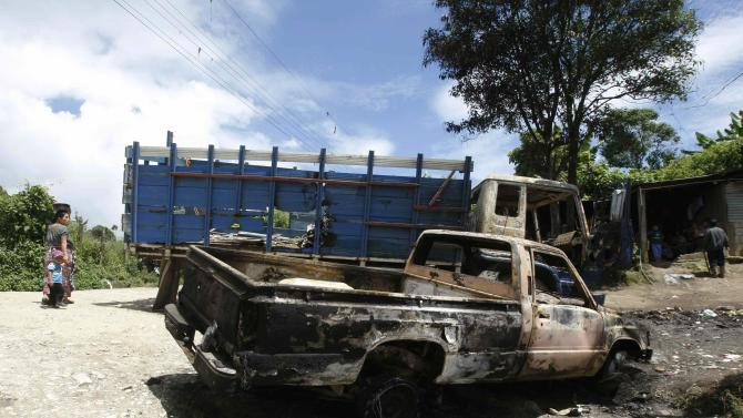 Burned vehicles are seen after clashes in Pajoques on the outskirts of Guatemala City