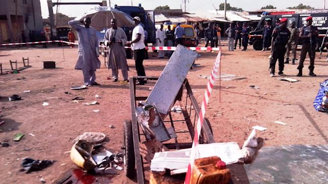 Police officers in Kano on July 24, 2014 stand near the mangled remains of a water dispenser in which an explosive was concealed
