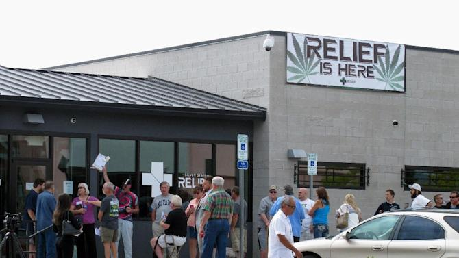 Dozens of people line up outside the Silver State Relief medical marijuana dispensary in Sparks, Nev., Friday, July 31, 2015, to be among the first in Nevada to legally purchase medicinal pot. Nevadans voted to legalize medical marijuana in 2000, but no language was in place to establish a system to sell or distribute it until 2013. (AP Photo/Scott Sonner)
