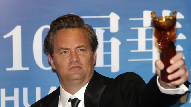 American-Canadian actor Matthew Perry poses with the trophy after winning the Best Global Actor in a TV Series at the 10th Huading Awards ceremony in Macau, Monday Oct. 7, 2013. (AP Photo/Vincent Yu)