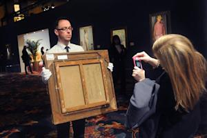 A staff member (L) of Sotheby's shows the back of a …