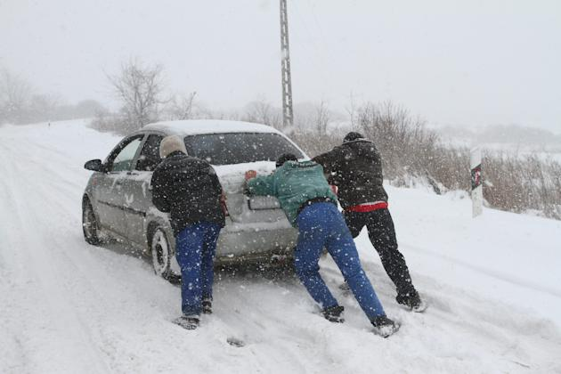 People push a car stranded by a heavy snowstorm on a road between Miskolc and Harsany, 155 kms northeast of Budapest, Hungary, Friday March 15 2013. Winter weather returning to Hungary with heavy snow
