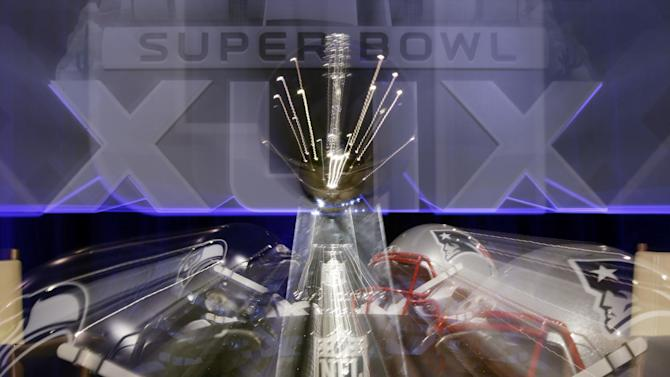 In this photo taken with a slow shutter speed, the Lombardi Trophy sits behind two helmets before a joint coaches news conference for NFL Super Bowl XLIX football game Friday, Jan. 30, 2015, in Phoenix