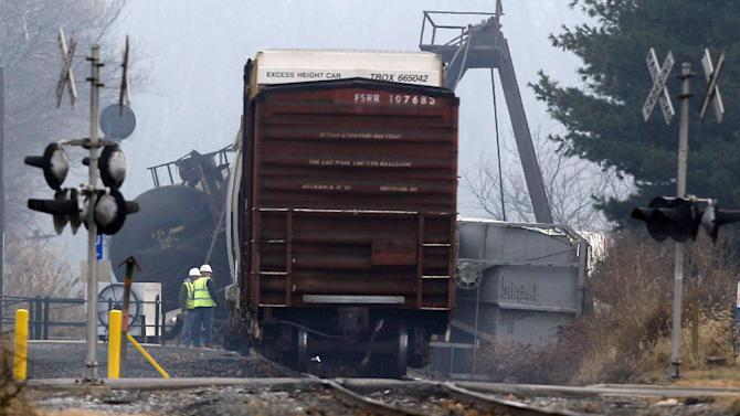 Officials stand next to derailed freight train cars in Paulsboro, N.J., Friday, Nov. 30, 2012. People in three southern New Jersey towns were told Friday to stay inside after the freight train derailed and several tanker cars carrying hazardous materials toppled from a bridge and into a creek. At least one tanker car may contain vinyl chloride, Gloucester County Emergency Management director J. Thomas Butts told WPVI-TV. (AP Photo/Mel Evans)