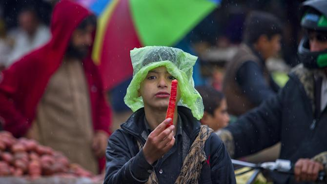A Pakistani boy displays a carrot in the rain to attract customers at a vegetable and fruit market on the outskirts of Islamabad, Pakistan, Sunday, March 1, 2015. (AP Photo/Anjum Naveed)