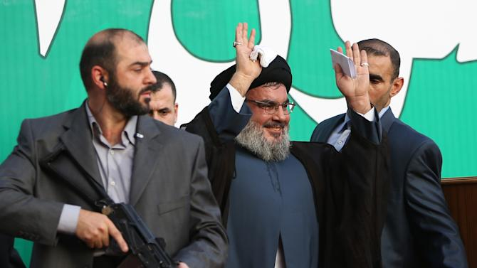 Hezbollah leader Sheik Hassan Nasrallah, center, escorted by his bodyguards, waves to a crowd of tens of thousands of supporters during a rally denouncing an anti-Islam film that has provoked a week of unrest in Muslim countries worldwide, in the southern suburb of Beirut, Lebanon, Monday Sept. 17, 2012. Nasrallah who does not usually appear in public for fear of assassination called for Monday's protests in Beirut, saying the U.S. must be held accountable for the film because it was produced in America. (AP Photo/Hussein Malla)