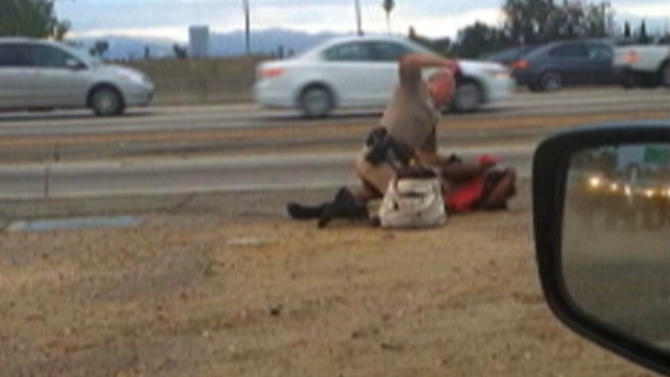 FILE - In this July 1, 2014 image made from video provided by motorist David Diaz, a California Highway Patrol officer straddles a woman while punching her in the head on the shoulder of a Los Angeles freeway. Attorneys for Marlene Pinnock, the woman who was seen on video being punched by a CHP officer, will hold a news conference Thursday, July 17, 2014 with updates on the case. CHP seized her medical records and clothing from the July 1 incident earlier this week. Pinnock's attorneys have said they're planning to file suit. (AP Photo/David Diaz,File)