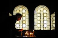 A sexton collects candles during a Christmas mass in the golden-domed Alexander Nevsky cathedral in central Sofia on December 25, 2012