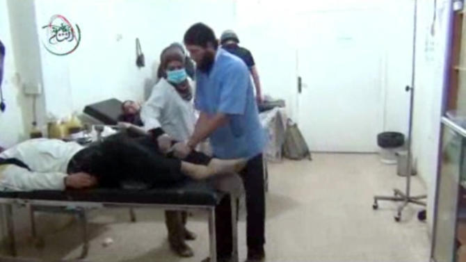 This undated image taken from amateur video footage provided by the Media Office Of Moadamiyeh purports to show medics assisting a man lying on a bed who appears to be shaking uncontrollably as a UN inspection team visits a makeshift hospital in Moadamiyeh, a suburb of the Syrian capital of Damascus. Doctors Without Borders said 355 people were killed in an artillery barrage by regime forces on Wednesday, Aug. 21, 2013 that included the use of toxic gas. The media office of Moadamiyeh is a loosely organized Anti-Assad activist group based in Moadamieyh which posts video and still images of violence and other developments from the region. The Associated Press cannot absolutely certify the content, date, location or authenticity of this image. (AP Photo/Media Office Of Moadamiyeh)